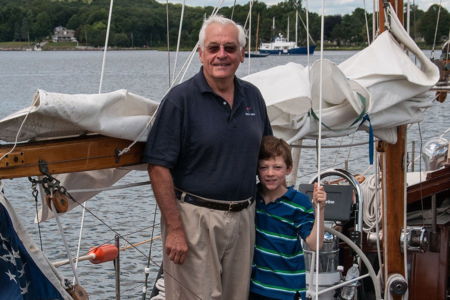 "J. Barclay Collins II with his grandson, Kai, on his boat, ""India."""